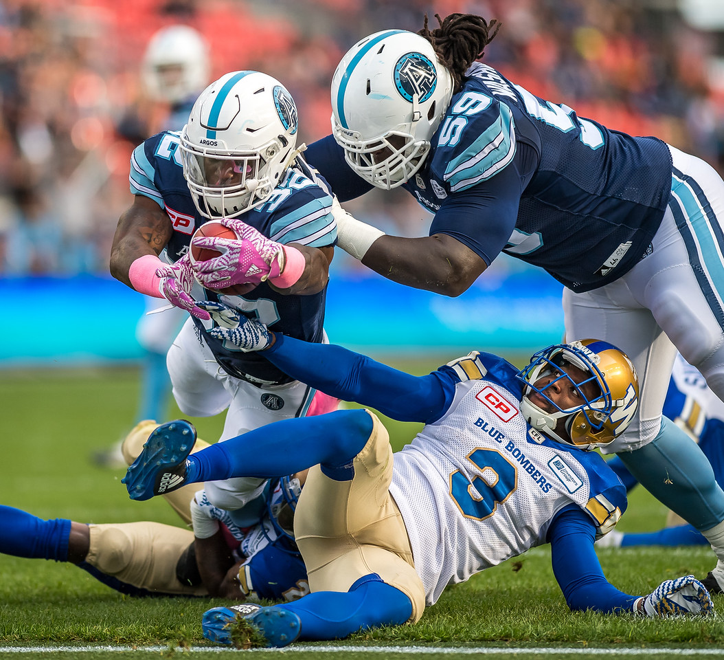 James Wilder Jr. (RB) evades the tackle by Kevin Fogg (DB) as he reaches for the goal line. Wilder Jr. finished with 18 carries and two touchdowns. Argos defeated the blue Bombers 29-28.