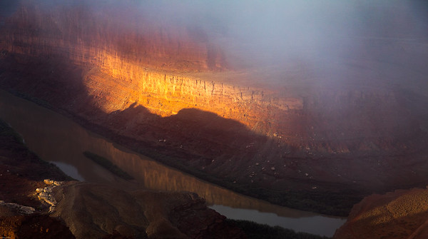 A sunbeam illuminates the Colorado RIver gorge as a fog rolls in above