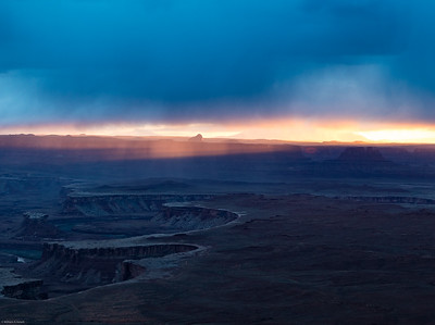 The sun peeks beneath the clouds at Green River Overlook, Canyonlands National Park