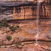 Monsoon waterfall over Ancestral Puebloan structure (near trees), Bears Ears National Monument and environs, San Juan County, Utah