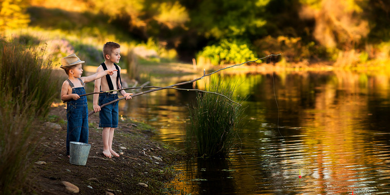Sacramento children photographer during outdoor portrait session. Kids pictures of two boys fishing by Bidun Studio Photography.
