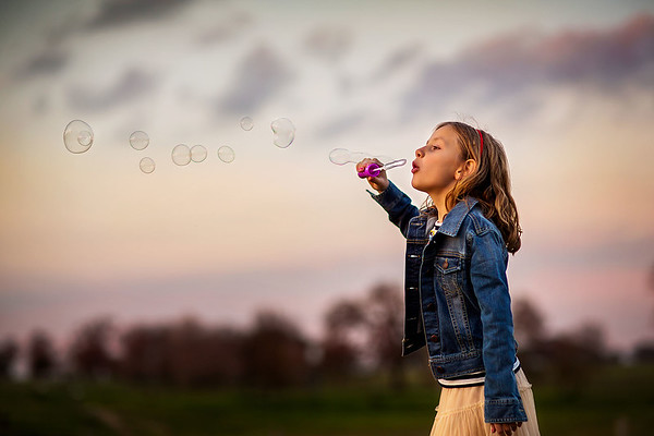 Sacramento children photographer during outdoor portrait session in a park with bubbles. Kids pictures by Bidun Studio Photography.