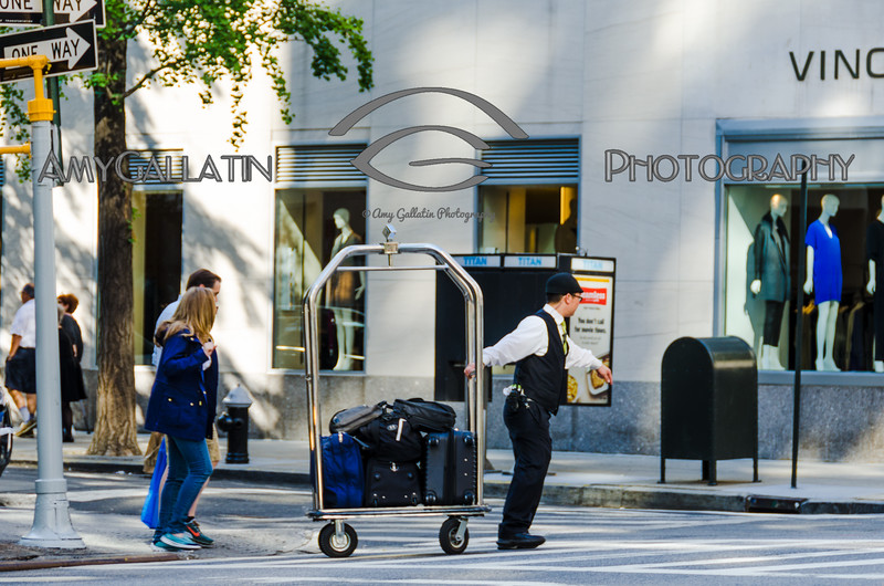 Bellman pulling a couple's luggage across city street