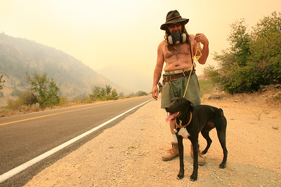 An armed transient walks his dog away from a massive fire.