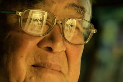 George Yoshitake examines a photo he took of an atmoic mushroom cloud.