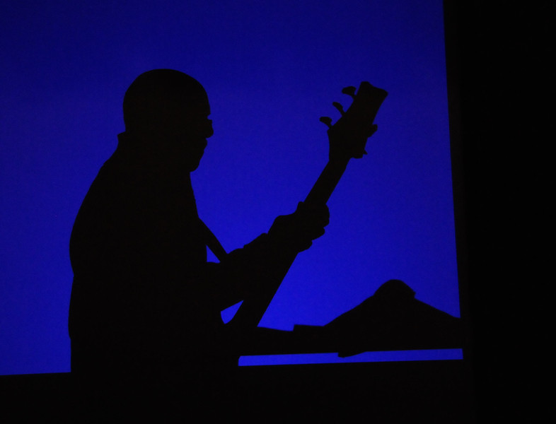 The Who Dat Band bassist silhouetted by blue light.