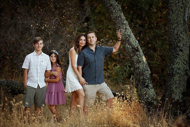 Sacramento family photographer during outdoor portrait session. Fall Folsom lake family portraits with long grass in a forest.