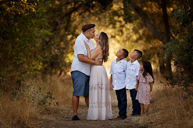 Family portrait photography at outdoor location by Sacramento top family photographer Sergey Bidun. Fall family session in a park.