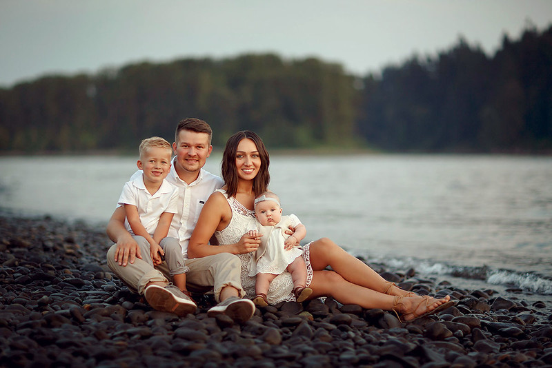Family portrait photography at outdoor location by Sacramento top family photographer Sergey Bidun. Cute family portraits on the rocks by a river.