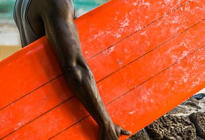 African-American surfer holding orange surfboard