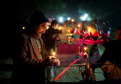 A man lights candles as part of preparations for the Mehndi ka Juloos, type of procession which commemorates the death of Qasim ibn Hasan ibn Ali ibn Abi Talib who was a Shia hero who died at the Battle of Karbala. This is one of the numerous Juloos, or processions during Moharram.