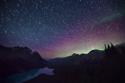 Star trails and aurora borealis over Peyto Lake, Alberta, Canada.