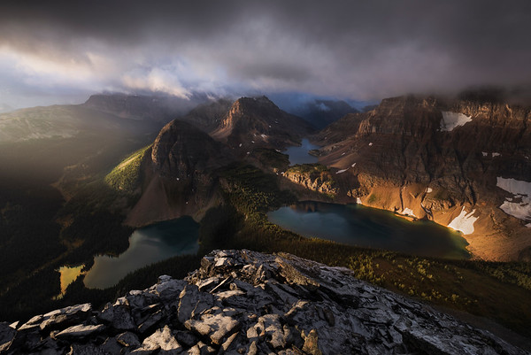 """Echo""  This photo is a result of a lot of different and strange circumstances lining up in unexpected ways. A couple days prior, Matt (Matt Jackisch Photography) and I had scrambled up this mountain to have a look at the view and learn the route, only to be caught inside a cloud at the summit. We waited as long as I could stand it (I was frozen as we huddled down beside a large rock that was acting as a windbreak) and had wrapped my emergency blanket around myself, but the cloud wasn't showing any sign of dissipating. Hands and feet numb, we decided to head down, disappointed.  We rested for a day before attempting the real goal, summiting for sunrise. We woke up at 3am, scarfed down breakfast, and made our way to the base of the mountain with our headlamps shining the way. This was the first time I'd ever attempted to attain a summit for sunrise, and I was equal parts excited about the prospect, and nervous about wandering around deep in the backcountry in the dark.  After accidentally passing the cairn which we were supposed to turn at to begin our ascent, we retraced our steps and then began our climb. It got cooler as we ascended, and pretty soon we realized it was snowing lightly.  First light came as we reached the ridge. The rocks were especially slippery with the fine dusting of snow; we had to make our way slowly and carefully upwards to avoid slipping.  Only about 20' away from the summit, I suddenly heard, in my mind, my dad's voice as clear as a bell. I'll keep what he said to myself, but it was a special moment for me because I've not heard his voice (even in recording) since he passed away two years ago today. Heart in my throat, I reached the cairn, touched it, and then settled in with my camera to witness one of the most spectacular and breathtaking sunrises I've ever seen in my entire life."