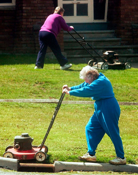 It's a job for two.  (Front) Nettie Sherman and her sister Kathryn Spangler take advantage of a warm spring day to neaten up Spangler's lawn on East State Street in Fremont.  Sherman was well equipped for the steep terrain, donning her golf spikes for the occasion.<br /> Photo Ben French<br /> 4/11/02<br /> The Fremont News Messenger<br /> Fremont OH