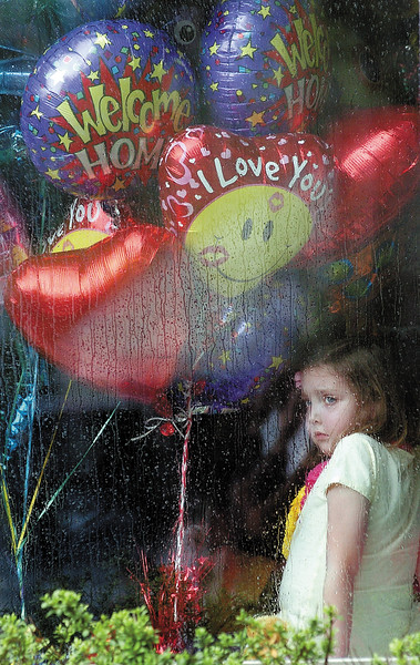News photo by Ben French<br /> Sophie Sheridan, 8, looks out of the window at her home on Wexford Road at friends and neighbors upon her return home last Thursday after getting a heart transplant.