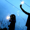 (L-R) Joshua Stoudinger (3), Taylor Holland (4), and Brent Holland (6) play with sparklers before the fireworks begin.<br /> Photo Ben French