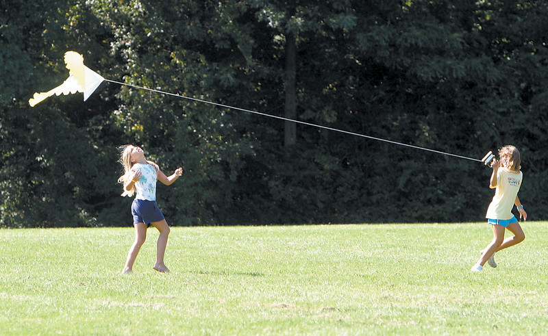 "News photo by Ben French<br /> <br /> Spirits are soaring<br /> Nine-year-olds Sarah Both (left) and Natalie Bayer attempt to fly a kite at Thompson Park during the Upper Arlington Parks and Recreation Department's ""Family Kites and Flight"" event Saturday morning."