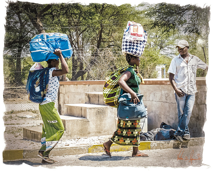 """WATCHING THE GIRLS WORK"" - SEVERAL NATIVE WOMEN CARRYING GREAT LOADS AND A MAN WATCHING AND ENJOYING THE ACTION AT THE BORDER BETWEEN ZIBABWE AND ZAMBIA"