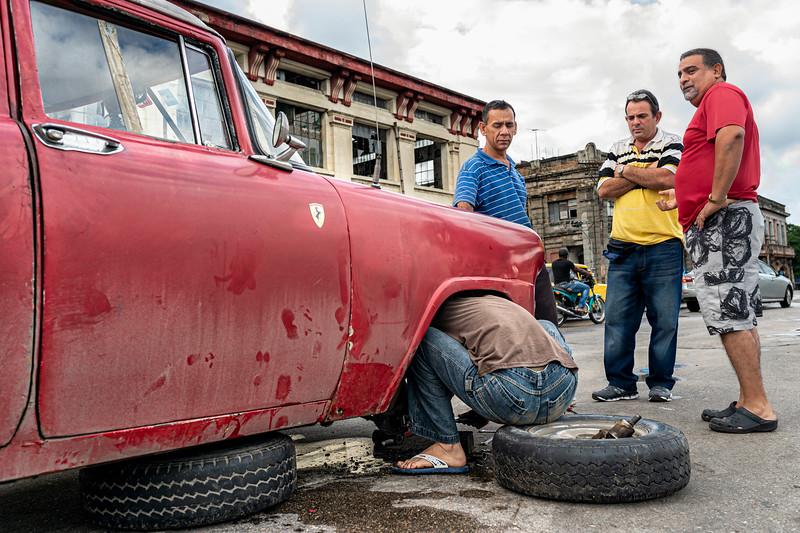 Three men look on while a man makes impromptu car repairs in the street in Havana, Cuba