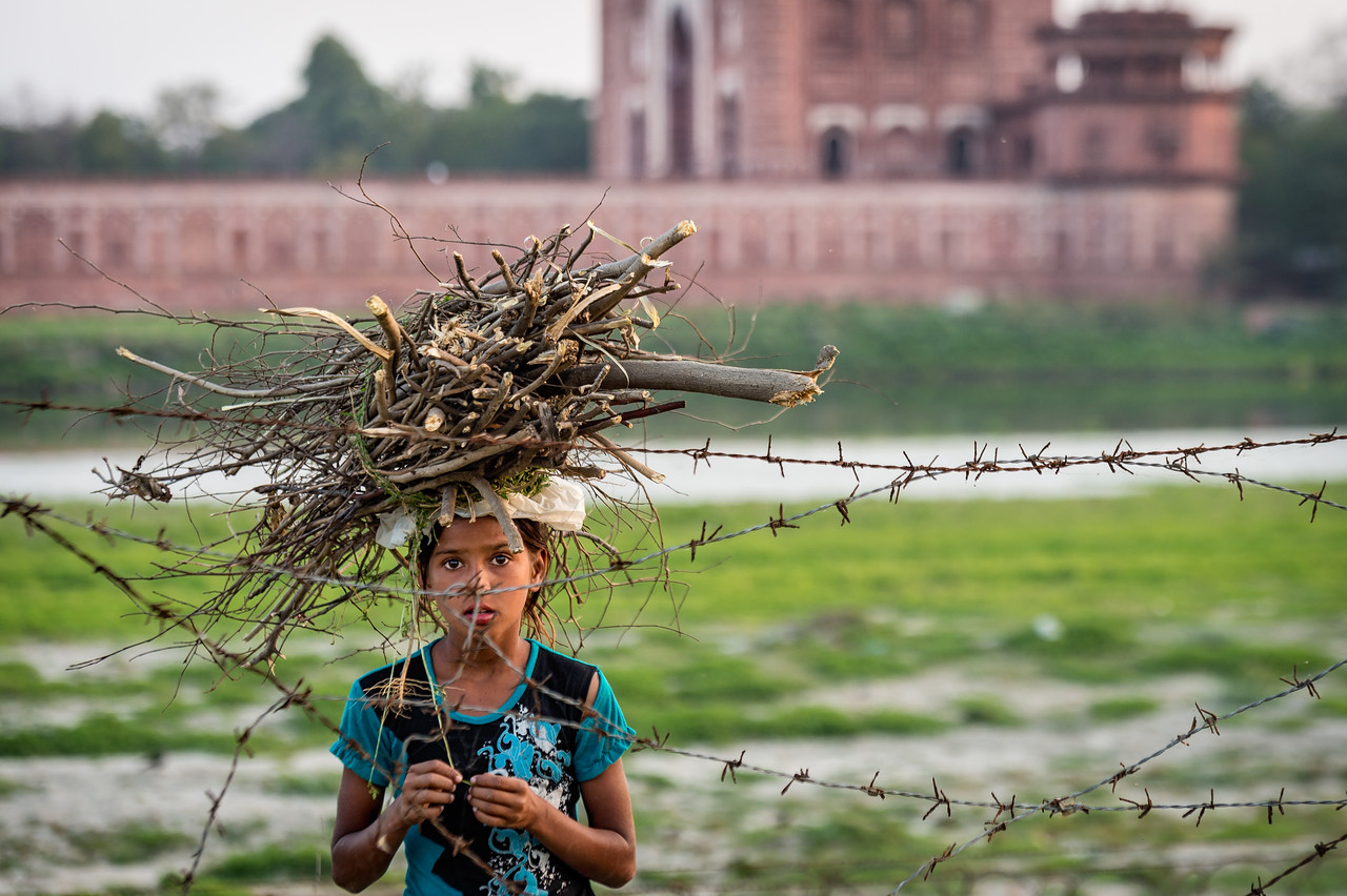 Curious young girl beyond the barbed wire behind the Taj Mahal