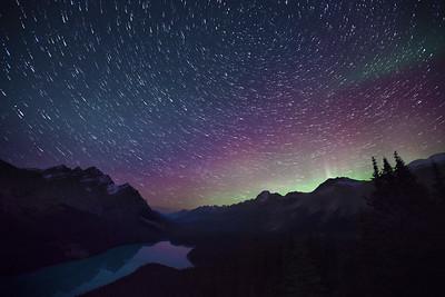 Star trails and aurora borealis over Peyto Lake, Alberta, Canada.