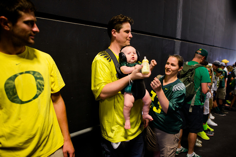 9-month-old Daphne Little is bottle-fed by her father Aaron in Autzen's west tunnel as her mother Janice looks on. The Oregon alumni parents ('03 and '02, respectively) outfit their infant daughter in a pair of noise-protectant headphone for Daphne's first Duck game. The No. 3 Oregon Ducks kick off their 2013 season against the Nicholls State Colonels in a pre-conference game on Aug. 31 in Autzen Stadium in Eugene, Ore.