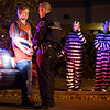 Jonny Williamson, 20, speaks with a Eugene Police officer in the intersection of 19th and Hilyard after being detained for disrupting traffic in Eugene, Ore. on Oct. 27, 2012. Williamsons' friends, from left, twins Cory and Justin Wetzel, and Mike Mcnall, had chosen prison outfits as their Halloween costumes, and they recorded the situation on their phones as it unfolded in front of them. Although Williamson was handcuffed and held for over 15 minutes, he was eventually released with only a warning, which he credited to his day's birthday luck.