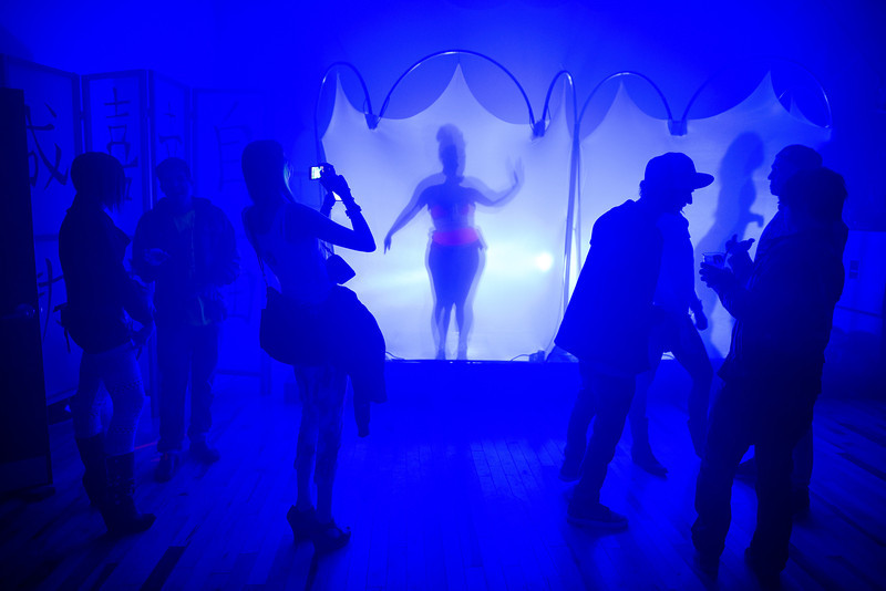 Burlesque performers dance behind translucent screens at the Glow Me concert and benefit show for Colby Hayden's birthday at Refuge in Portland, Ore. on March 23, 2013.
