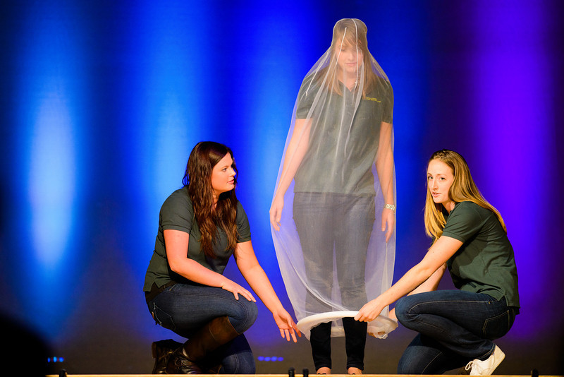 Olivia Gust, far left, demonstrates how to fit a condom onto her subject Sarah Sprague, center, as Ellen Price looks on. The trio are peer health educators from the University's Health Center. The Cultural Forum put on the annual Condom Fashion show in the EMU Ballroom to promote safer sex on Oct. 25, 2013 in Eugene, Ore.