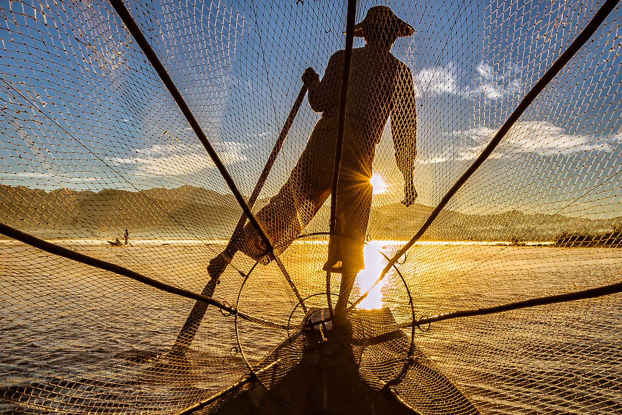 Fisherman rowing towards the sunset at Inle Lake, Myanmar