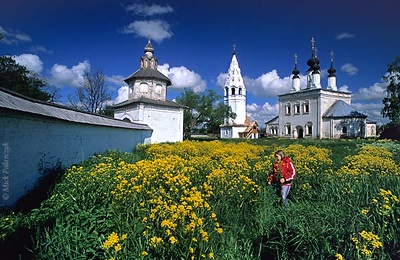 [RUSSIA.GOLDENRING 25.991] 'Alexandrovski Convent.'  	In the grounds of Suzdal's Alexandrovski Convent a girl is picking cole-seed flowers. The Ascension Church and the bell-tower were built in the 17th century. The surrounding wall and leaning Holy Gate on the left date from the 18th century. Photo Mick Palarczyk.