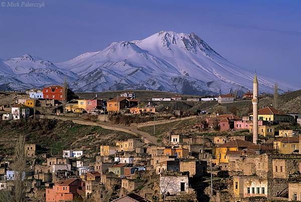 [TURKEY.CENTRAL 26923 'Village under the volcano.'  Spring snow still covers the slopes of the Hasan Dag volcano, looming behind the Cappadocian village of Ihlara. The Hasan Dag is one of the volcanos that were responsible for covering the region with ash, resulting in the spectacular tuff formations for which Cappadocia is famous. Photo Mick Palarczyk.