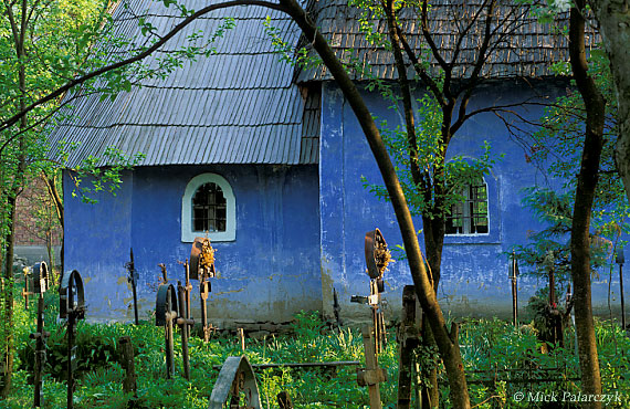 [ROMANIA.MARAMURES 23.675] 'Colourful church.' The church of Strîmtura shimmers as a blue pearl behind the green foliage of its churchyard. Photo Mick Palarczyk.