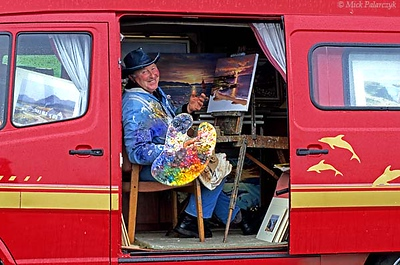 [BRITAIN.IRELANDNOR 21.857] 'Rainy sunset.' Sheltering in his van at White Park Bay near Ballintoy, the pooring rain doesn't prevent this seascape painter from creating a colourful sunset on his canvas. Photo Mick Palarczyk.