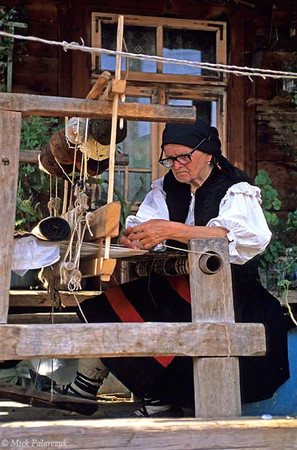 [ROMANIA.MARAMURES 23.747] 'Weaving on the verandah.' Working on an old loom in front of her house this inhabitant of Botiza village uses wool that has been coloured by plant extracts. Photo Mick Palarczyk.