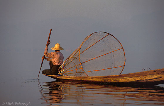 [BURMA 24.834] 'Searching for fish (2).' While the first sun-rays are piercing the haze over the Inle Lake, an Intha fisherman searches the lake for a catch. Photo Mick Palarczyk.