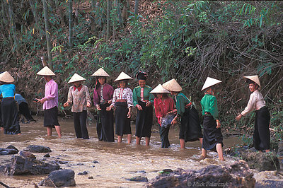 [VIETNAM.NORTH 21.297] 'Handing down boulders.' Black Thái tribes women hand down river boulders which are used to build a dam for an irrigation wheel. (See image 21.293). Photo Mick Palarczyk.