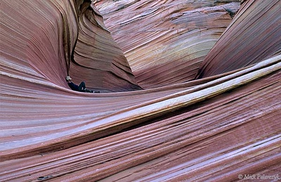 "[USA.ARIZONA 28007] 'Taking a nap in The Wave.'  	The hiker who enters ""The Wave"" in the Coyote Buttes nature reserve (part of the Vermilion Cliffs Wilderness) may find himself surrounded by a dream-like sandstone landscape. The fine layers of the stone are composed primarily of wind-blown sand from a vast ancient desert. Photo Mick Palarczyk."