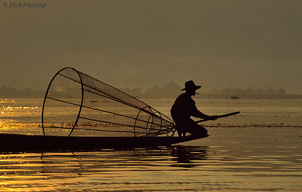 [BURMA 24.831] 'Searching for fish (1).'	 While the first sun-rays are piercing the haze over the Inle Lake, an Intha fisherman searches the lake for a catch. Photo Mick Palarczyk.
