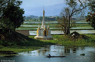 [BURMA 24.820] 'Pagoda near Nampan village.'	 At the Inle Lake near Nampan village a narrow strip of land carries an enchanting pagoda. In the background shimmer the mountains of the Shan highlands. Photo Mick Palarczyk.