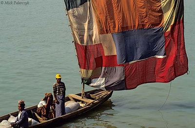 [BURMA 24.980] 'Sailing on the Chindwinn River.'	 At Monywa, a boat on the Chindwinn River carries a sail which has been sewn together from different pieces of colourful cloth. Photo Mick Palarczyk.
