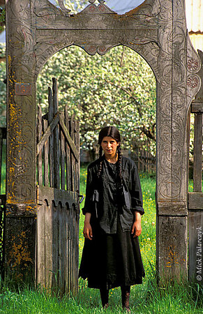 [ROMANIA.TRANSYLVA 24.134] 'Roma girl.'	 Roma girl at Valea Strîmba standing in a decorated gate typical of the houses of the Hungarian minority living in the region around Georgheni. Photo Mick Palarczyk.