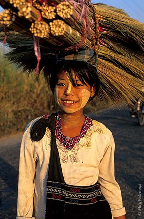 [BURMA 24.747] 'Girl with brooms.'	 On a road north of Taungoo, this girl, her face enlivened by thanaka make-up, is on her way to sell little brooms at the market. Photo Mick Palarczyk.
