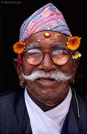 [NEPAL.KATHMANDUVALLEY 27314] 'Pensioner in Patan.'  	Flowers, earrings and red-yellow tika on his forehead give this pensioner of Patan colourful appearance. Photo Mick Palarczyk.
