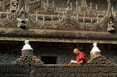 [BURMA 25.098]<br /> 'Studying monk.'<br /> <br /> 	Amid precious woodcarvings a young monk is studying on the elevated platform surrounding the Mandalay Shwenandaw Monastery. Photo Mick Palarczyk.