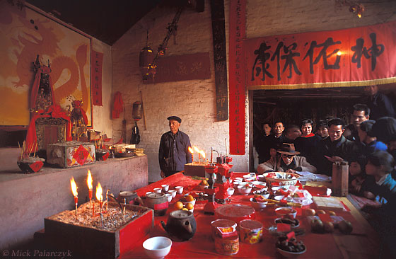 <h4>[CHINA.GUANGXI 25.277] <br>'Fortune-teller.'	</h4> At San Wang Miao, a village of the Miao mountain tribe, tribe-members gather around the offering-table in the village temple during New Year festivities. The fortune-teller of the village is seated at the table by a large book with spells.  Photo Mick Palarczyk.