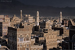 [YEMEN.NORTH 26463<br /> 'Dark sky above Sana .'<br /> <br /> The two white minarets (on the right) of Sana's Big Mosque catch the rays of a late afternoon sun while a thunderstorm is descending on the city from the east. Photo Mick Palarczyk.