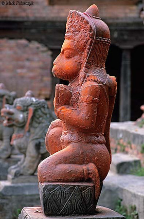 [NEPAL.KATHMANDUVALLEY 27415]<br /> 'Hanuman on Bhaktapur's Maheshwari Ghat.'<br /> <br /> 	A statue of the Hindu ape-god Hanuman has been smeared with orange powder and decorated with holy threads. The statue can be found on the Maheshwari Ghat along the Hanumante River in Bhaktapur. Owing to his ability to ward of evil spirits, Hanuman is one of the most popular gods in Nepal. Photo Mick Palarczyk.