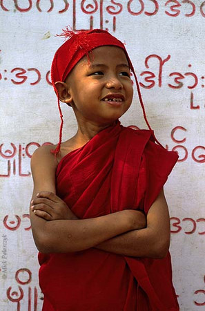 <h4>[BURMA 25.036] <br>'Young monk at Sagaing.'	</h4> This young monk is standing in front of a slab that records the names of people that have donated money to local temples at the foot of Sagaing Hill. Photo Mick Palarczyk.