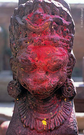 [NEPAL.KATHMANDUVALLEY 27413]<br /> 'Statue in Bhaktapur's Wakupati Temple.'<br /> <br /> The coloured powder on this statue in the courtyard of Bhaktapur's Wakupati Narayan Temple has been smeared across its face by the rain. Photo Mick Palarczyk.